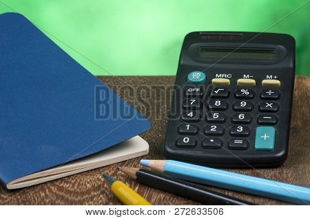 Notebook With A Calculator And Some Pencils On A Bench And Green Background.