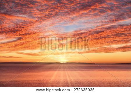 Dramatic, Fiery Yellow, Golden, Red And Magenta Sunrise Sky With Sun And Sun Rays Over The Sea.