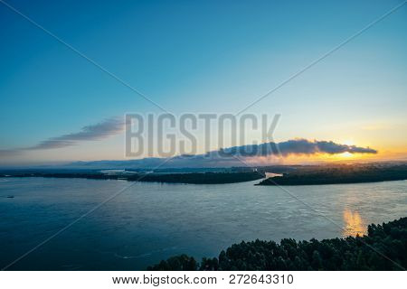 Broad river. Riverbank with forest and fog. Orange glow from dawn reflected in water. Sun shines through cloud of snake or crocodile shape. Mystical morning atmospheric landscape of majestic nature. poster
