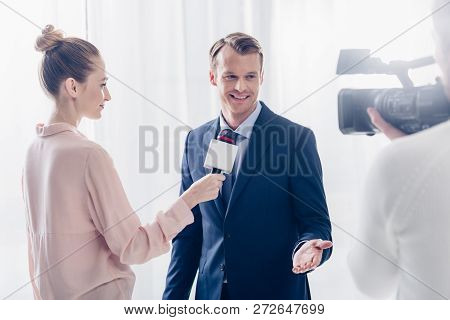 Smiling Handsome Businessman Giving Video Interview To Journalist In Office