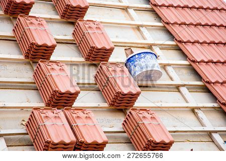Roofer working on roof structure of building on construction site poster