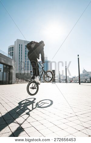 Bmx Rider Jumps On A Bike On A Sunny Day, Against The Backdrop Of Urban Scenery.bmx Concept. Street