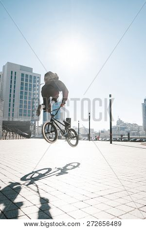 BMX freestyle. BMX cyclist makes complex tricks on a bike. Young man makes spectacular stunts against the background of the city square. poster