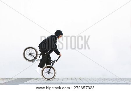 Bmx Racer Makes A Trick In Against The Background Of A White Wall. Bmx Rider With A Bicycle In Fligh