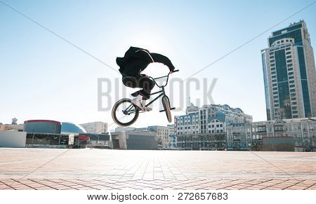 Silhouette Of A Bmx Rider Jumping Against The Backdrop Of The Sun And Urban Landscape On A Bright Su