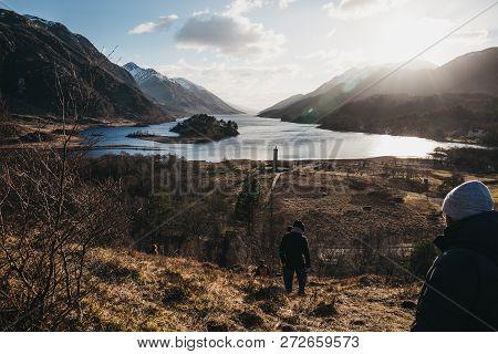Glenfinnan, Scotland - March 17, 2018: People Hiking In Glenfinnan, Glenfinnan Monument On The Backg