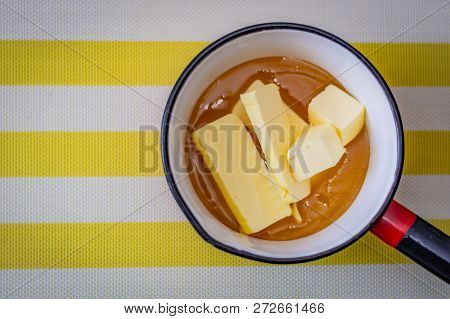 Cubes Of Butter Embedded In Honey In A Saucepan Ready To Be Heated For Baking