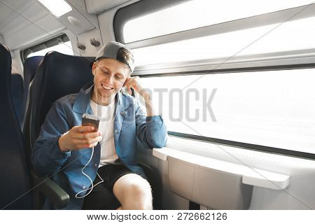 Smiling Tourists Travel By Train And Listens To Music In The Headphones And Looks At The Smartphone.