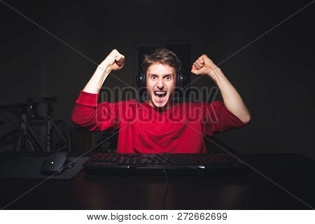 Portrait Of An Emotional Gamer Rejoicing With His Hands Up. Young Man Sits At Night, But Uses A Comp