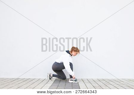 Sports Girl Cords Sneakers On The Background Of A White Wall. Young Girl Playing Outdoor Sports, Bac