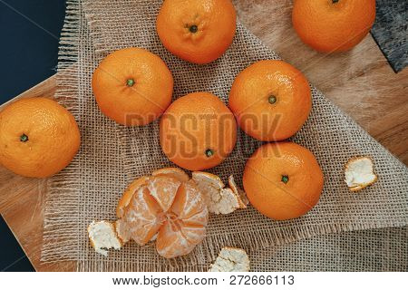 Bright Orange Tangerines (clementines) Whole And Peeled With Rind On A Wooden Background With Burlap