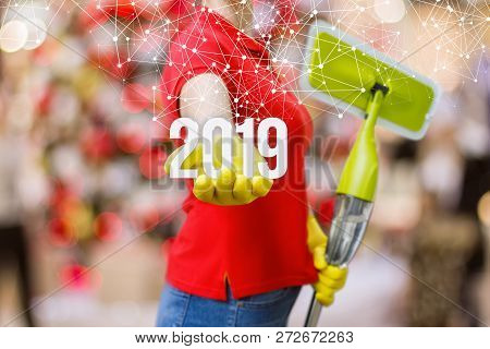 A Cleaning Woman In Rubber Gloves With A Mop In One Hand Is Showing The Numbers Of Coming Year In Th