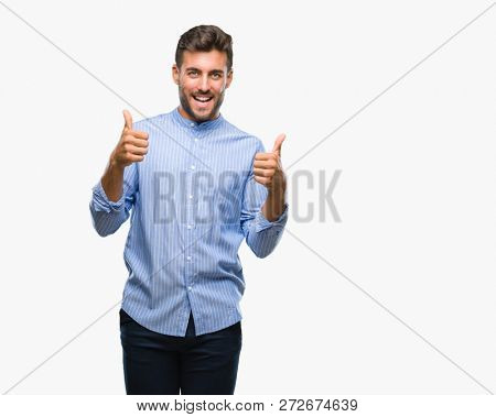 Young handsome man over isolated background success sign doing positive gesture with hand, thumbs up smiling and happy. Looking at the camera with cheerful expression, winner gesture.