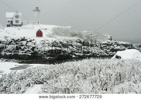 Snow Covered Nubble Lighthouse, Or Cape Neddick Light, Sits Atop A Rocky Island During A Windy Snows