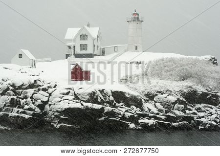Nubble Lighthouse, Also Known As Cape Neddick Light, Flashes Its Red Light During A Blizzard Snowsto