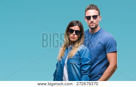 Young couple in love wearing sunglasses over isolated background with serious expression on face. Simple and natural looking at the camera.
