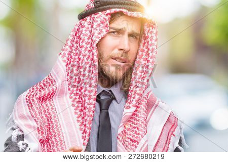 Young handsome arabian man with long hair wearing keffiyeh over isolated background disgusted expression, displeased and fearful doing disgust face because aversion reaction. With hands raised