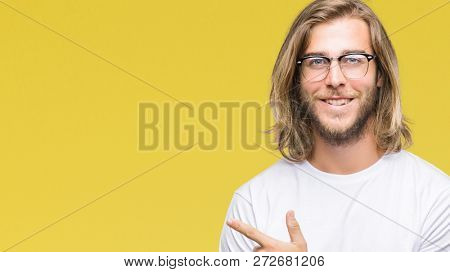 Young handsome man with long hair wearing glasses over isolated background cheerful with a smile of face pointing with hand and finger up to the side with happy and natural expression on face
