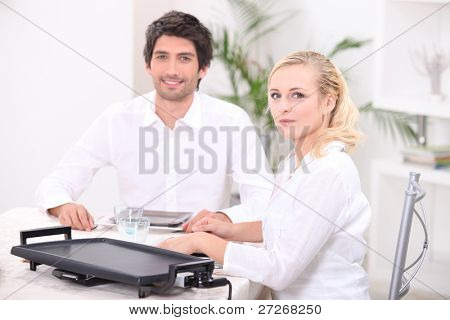 Couple using an electric tabletop hotplate
