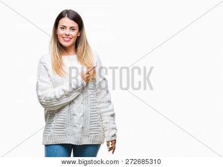 Young beautiful woman casual white sweater over isolated background cheerful with a smile of face pointing with hand and finger up to the side with happy and natural expression on face looking