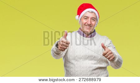 Handsome senior man wearing christmas hat over isolated background approving doing positive gesture with hand, thumbs up smiling and happy for success. Looking at the camera, winner gesture.