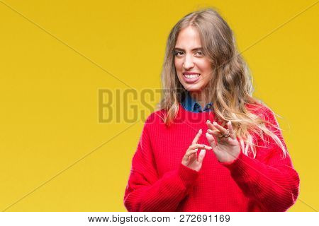 Beautiful young blonde woman wearing winter sweater over isolated background disgusted expression, displeased and fearful doing disgust face because aversion reaction. With hands raised. Annoying