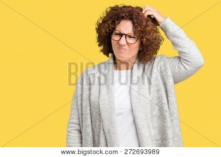 Beautiful middle ager senior woman wearing jacket and glasses over isolated background confuse and wonder about question. Uncertain with doubt, thinking with hand on head. Pensive concept.