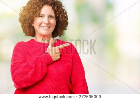 Beautiful middle ager senior woman red winter sweater over isolated background cheerful with a smile of face pointing with hand and finger up to the side with happy and natural expression on face