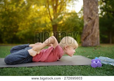 Little Boy Doing Stretch During Workout Outdoors. Healthy Lifestyle For Kids.