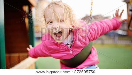 Cute Little Girl Having Fun On Outdoor Playground. Spring/summer/autumn Active Sport Leisure For Kid