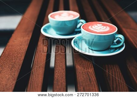Two Cups Of Living Coral Cappuccino On Wooden Background. Beautiful Foam, Greenery Ceramic Cups. Col