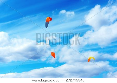 Four Bright Multicolored Sports Kites For Kiting Or Snowkiting Against The Blue Sky. Kite Surfing On