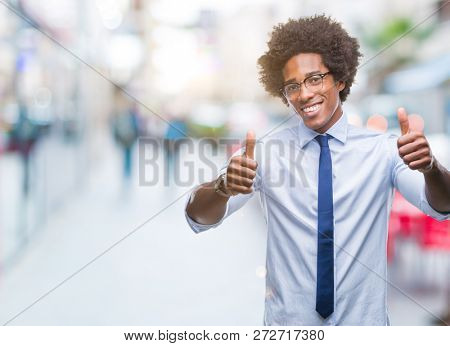Afro american business man wearing glasses over isolated background approving doing positive gesture with hand, thumbs up smiling and happy for success. Looking at the camera, winner gesture.