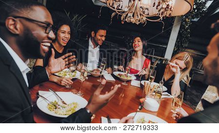 Friends Chilling Out Enjoying Meal In Restaurant. Group Of Happy Friends Meeting And Having Dinner.