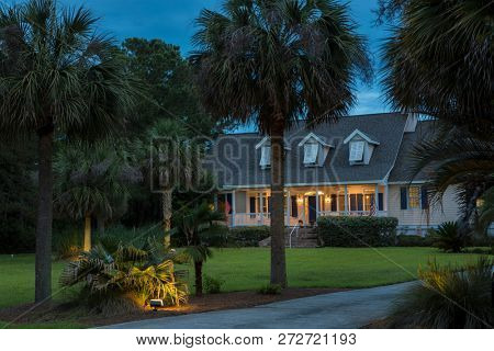 Beautiful cape cod house lit up at twilight with palm trees.