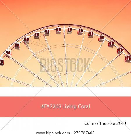 An old-fashioned ferrir wheel as an example of the trend colour of the year 2019, Living Coral, with corresponding colour hex code.
