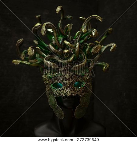 poster of Head Medusa, creature of Greek mythology. pieces made by hand with goldsmiths and metals such as gold and copper. wears a helmet of green and gold snakes