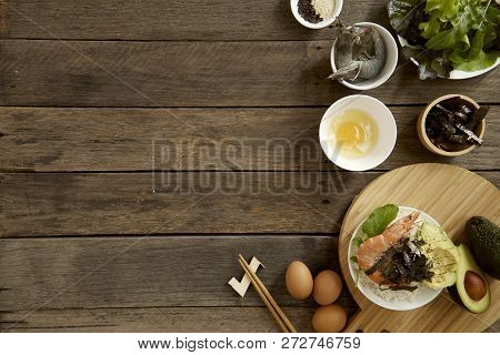 Avocado Hawaii food poke bowl Composition of kitchen devices on wooden table, Healthy Food Concepts, free copy space, flat lay food poster