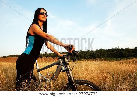 Portrait of pretty young brown haired woman riding a bike with text space
