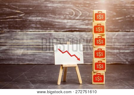 Wooden Cubes With The Image Of The Dollars And The Arrow Down. Financial And Economic Crisis. Drop I