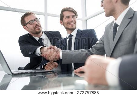 handshake business partners sitting at the office table