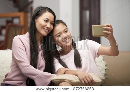 Beautiful Asian Adult Woman With Charming Teen Girl Sitting On Sofa And Taking Selfie With Phone