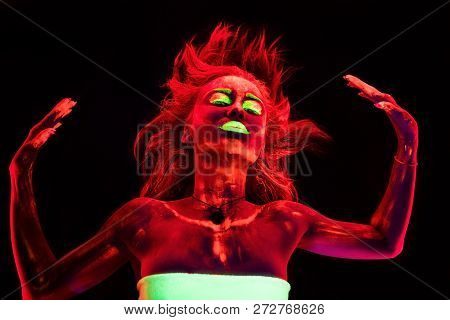 Portrait of a suffering young sexy girl on black background with ultraviolet paint on her body. Pretty woman with glowing bodyart in black lamp light poster