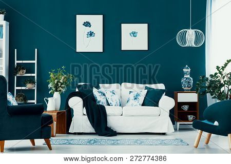 Floral Poster On Emerald Wall In Chic Living Room Interior With White, Blue And Wooden Furniture In