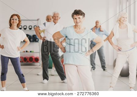 Smiling Elderly Woman Holding Hips During Gymnastic Classes For Senior People