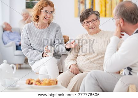 Group Of Elderly People Talking And Enjoying Each Other's Company At Senior Club