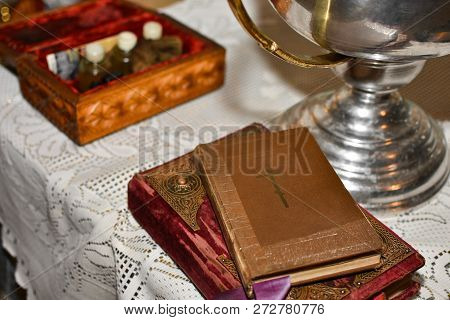 Bible Lies On The Table With The Cup In The Church Before The Rite Of Baptism