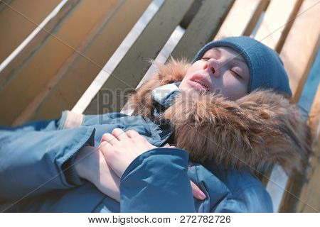 Woman Became Ill, Lying On A Park Bench In Winter, And Breathing Heavily.