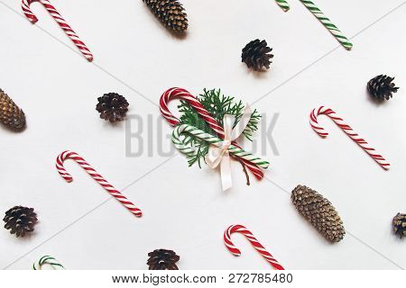 White Wooden Background With Red And Green Christmas Candies And Conifer Cones