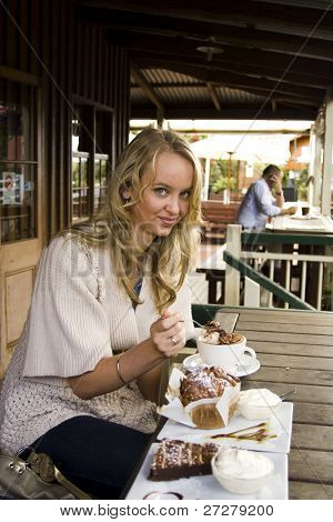 young girl at a cafe eating cake and drinking coffee